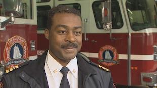 Corey Beals souriant devant des camions de lutte contre les incendies