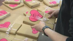 main tenant un livre emballé avec un etiquette en forme de coeur.