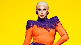 Brooke Lynn Hytes porte une tenue orange et violette et pose devant un fond jaune.