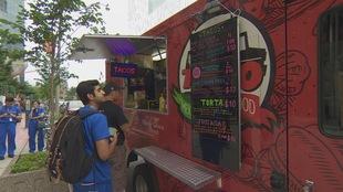 Des gens commandent à manger devant un camion de cuisine de rue