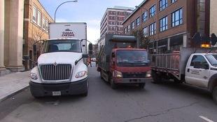 Deux camions de livraison circulent sur une rue à Montréal