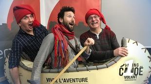 Nicholas Fish, Rudy Desjardins et Martin Flibotte portent tuques et foulard rouges et tiennent le canot du Canoë Volant.