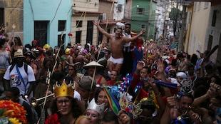 Des festivaliers costumés qui prennent part au Carnaval de Rio défilent dans les rues.