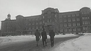 Photo en noir et blanc de personnes qui marchent devant le Cégep de Chicoutimi.