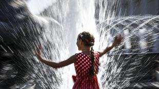 Une jeune fille avec une robe rouge à pois joue dans une fontaine d'eau.