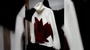 Une chandail à col roulé en laine polaire arbore une feuille d'érable rouge en fourrure.