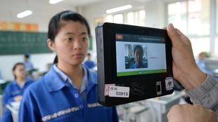 Une personne tient une petite machine qui est épaisse et qui a un écran au centre devant une jeune Asiatique. Le visage de la jeune femme apparaît sur l'écran.