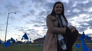 Chloé Perreault devant un champs de petit drapeaux bleus.