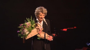Clémence DesRochers, sur scène, remercie le public avec des fleurs dans les bras.