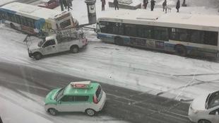 Une camionnette portant une échelle se trouve au milieu de la rue après avoir été emboutie par un autobus de la STM, sur une chaussée glissante et enneigée. Un taxi Téo tente aussi de se redresser après avoir perdu le contrôle.