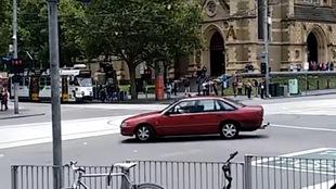 Une voiture rouge tourne en rond devant une gare de Melbourne sous le regard de passants inquiets