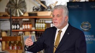 Philippe Couillard, dans un bâtiment de ferme, présente son plan bioalimentaire.