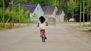 Une fillette sur son vélo au milieu d'une rue sur laquelle circule aussi une camionnette.