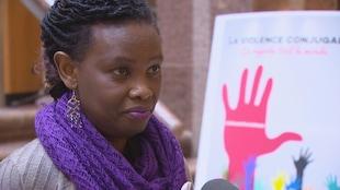 Dada Gasirabo devant une affiche de la campagne de sensibilisation contre la violence faite aux femmes.