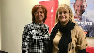 Diane Dallaire et Claire Bolduc devant l'affiche d'ICI Abitibi-Témiscamingue dans notre station.