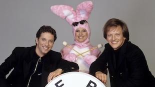 À l'intérieur, sur un fond neutre, les comédiens Patrice L'Écuyer et André-Philippe Gagnon entourent Dominique Michel déguisée en lapin Energizer.