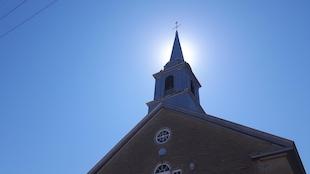 Le clocher d'une église sur fond de ciel bleu.