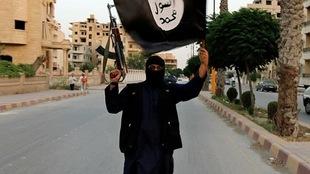 Un membre du groupe armé État islamique brandit un drapeau et son arme.