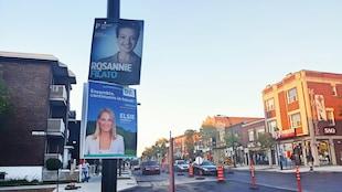 Deux pancartes montrant chacune une femme souriant à la caméra devant un fond bleu sont accrochées sur un poteau en bordure de la rue.