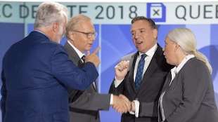 Les quatre candidats sont sur le plateau du débat et se serrent la main.