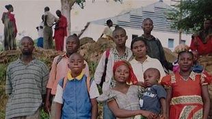 Des jeunes hommes et femmes et des enfants posent en groupe.