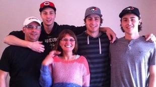 Une famille de cinq sourit à la caméra.
