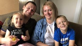 Une famille souriante est assise sur un canapé : une petite fille, un homme, une femme et un petit garçon.