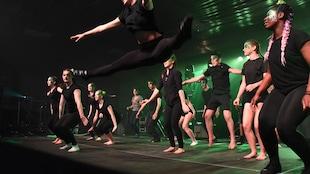De jeunes danseurs sur la scène habillés collants et teeshirts noirs. Une jeune femme au premier plan saute en faisant le grand écart dans les airs.