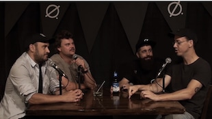 4 humoristes discutant autour d'une table avec des micros.