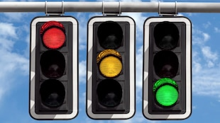 Une photo montrant trois feux de circulation suspendus côte à côte. Le premier affiche un feu rouge, le deuxième un feu jaune et le troisième un feu vert.