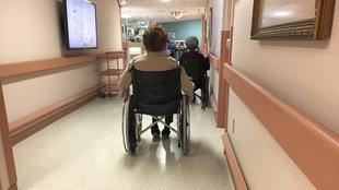 Deux dames âgées se déplacent en fauteuil roulant dans un couloir d'un foyer de soins.