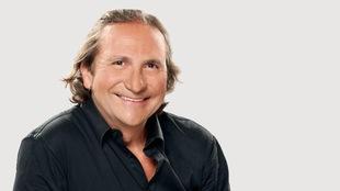 Franco Nuovo souriant et portant une chemise noire échancrée.