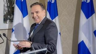 François Legault tient un document en regardant la caméra, derrière un podium.