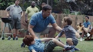 Un homme séparant deux garçons en train de se chamailler.