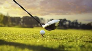un baton de golf s'apprête à heurter la balle au sol.