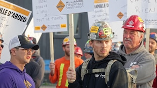 Des travailleurs bloquent l'accès à un chantier à Montréal.
