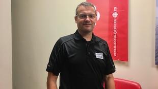 Benoît Tremblay pose devant une affiche de Radio-Canada Abitibi-Témiscamingue.