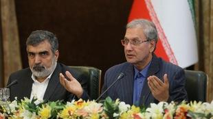 Deux hommes en costume cravate tiennent une conférence de presse.