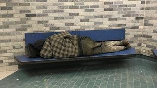 Un itinérant dormant sur un banc dans le métro Place-des-Arts à Montréal