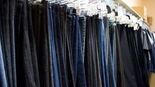 Plusieurs paires de jeans rangées dans une garde-robe.