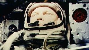 Une photo d'archives de la NASA montrant John Glenn dans son habit d'astronaute, entouré d'équipements, à bord d'un vaisseau spatial.