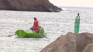 Deux hommes rament hors d'une baie rocheuse.