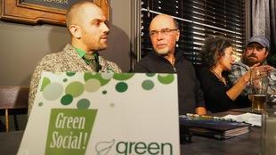 Les deux hommes sont attablés, et en avant-plan, une affiche, sur laquelle il est écrit : «Green Social».