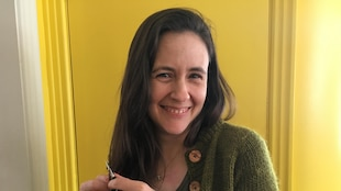 Karine Gallant avec un tricot dans les mains et des aiguilles de tricotage