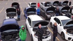 Ils sont réunis dans un stationnement, posant aux côtés de leur véhicule le capot ouvert.