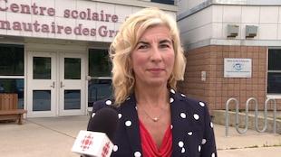 Kim Christianson devant une le Centre scolaire et communautaire des Grands-Vents, à Saint-Jean de Terre-Neuve, le 28 août 2018.