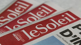 Trois éditions du journal sur une table. Gros plan sur le titre du journal.