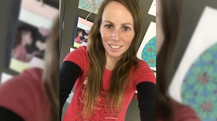 Une femme prend une photo d'elle-même, souriante.