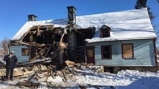 M. Picard regarde le sol, café à la main, devant la maison partiellement détruite.
