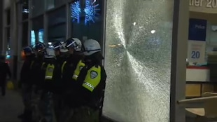 Des policiers devant la vitrine fracassée du poste de quartier 20 à Montréal